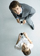 Business associates holding cups of coffee, looking up at camera, full length, high angle view
