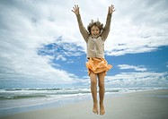 Girl jumping on beach, full length