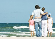 Family standing next to surf, facing ocean, rear view