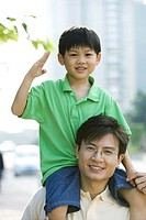 Man carrying son on shoulders, boy making gesture