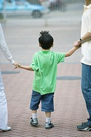 Boy holding parents' hands