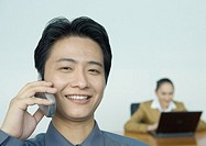 Businessman using cell phone, colleague working in background, portrait