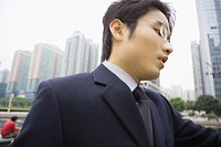 Businessman looking down, high rises in background