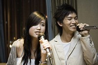 Young couple singing karaoke