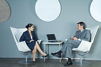 Businessman and businesswoman sitting face to face, having discussion