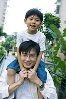 Boy riding on father´s shoulders, front view, smiling at camera
