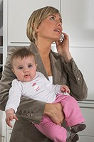 portrait of young businesswoman holding baby while talking on mobile phone