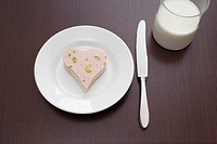 still life of sandwich with sausage cut out in shape of heart on plate and glass of milk