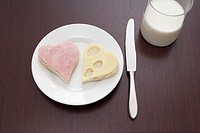still life of ham and cheese sandwich cut out in shape of heart on plate and glass of milk