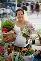 Young pregnant woman at vegetable market, holding groceries and flowers