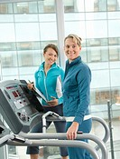Woman with personal trainer in health club, portrait