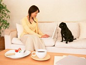 Woman using laptop on sofa with dog