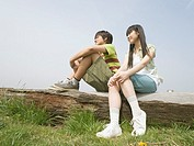 Boy and girl sitting on the lying tree in the field