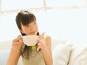 Girl drinking a cup of caffellatte on the sofa