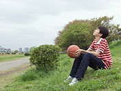 Sitting boy holding a basketball in the field