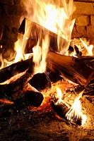 fire in stone or brick fireplace, glowing coals, yellow-white flames all over wood