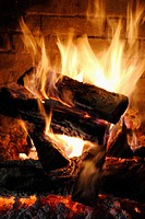 fire in stone or brick fireplace, glowing coals, plentiful yellow and white flames