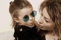 Young girl, wearing sunglasses, sitting with her mother.