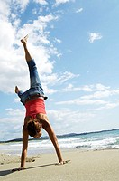 Rear view of woman doing cartwheel on beach