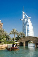 Tourists in boat with hotel in background, Burj Al Arab Hotel, Dubai, United Arab Emirates