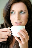 Close_up of young woman drinking coffee