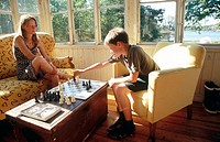 Playing chess, children and adults on the summer balcony