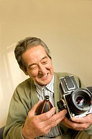 A Senior Adult Man Caring His Camera, Front View