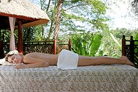 A young topless woman lying on massage table