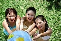 Portrait of three teenage girls with globe in garden (thumbnail)