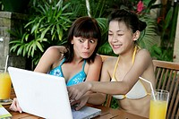 Portrait of two teenage girls looking at a laptop