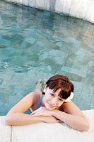 View of a teenage girl leaning by a swimming pool