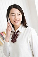 Girl using mobile phone, smiling, front view
