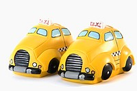 Close-up of two toy taxis parked side by side