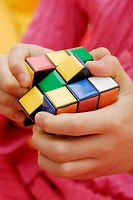 Mid section view of a person playing with a puzzle cube