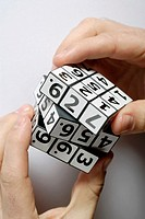 Close-up of a person's hands playing with a puzzle cube