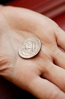 Close-up of an American dollar coin on a person's hand