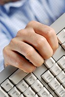 Close-up of a person's hand holding a computer keyboard