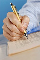Close-up of a person's hand writing with a ballpoint pen on a sheet of paper