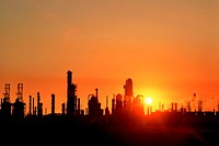 Chemical refinery plant and smokestacks in silhouette