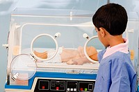 Close-up of a boy touching a baby boy in an incubator