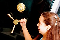 Side profile of a girl holding the handle of a safe