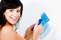 Portrait of a young woman holding a color swatch against a wall