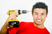 Portrait of a young man holding a drill machine against his head