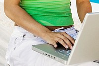 Mid section view of a woman using a laptop