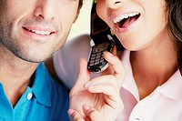 Close-up of a young couple using a mobile phone