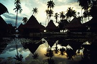 Reflection of huts and trees in water, Huahine Island, French Polynesia