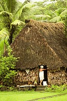 Rear view of a woman standing at the door of hut, Vanua Levu, Fiji