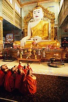Rear view of monks praying in front of a statue of Buddha, Sagaing, Myanmar