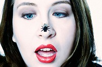 This stock photo shows an attractive young woman, age 20_25, looking with crossed blue eyes at a plastic fly on her nose