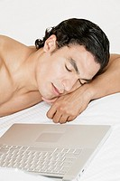 Young man sleeping in front of a laptop